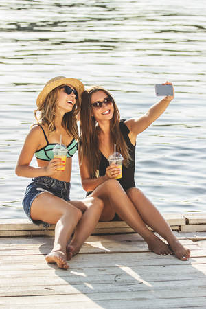 Selfie with the best friend. Two cheerful and young women in swimsuits are taking selfie with lemonade on the smart phone while having fun on wooden pier. Zdjęcie Seryjne