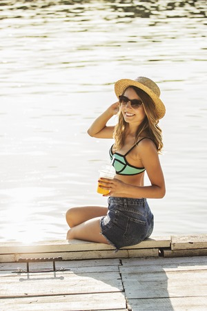 Young and beautiful beach girl. Side view of beautiful and young woman in swimsuit and sunglasses keeping glass with lemonade in hand and smiling while sitting on wooden pier. Zdjęcie Seryjne