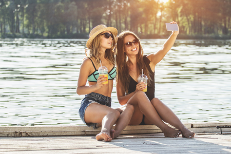 Selfie with the best friend. Two young and beautiful women in swimsuits taking selfie with lemonade glasses and smiling while sitting on wooden pier. Zdjęcie Seryjne