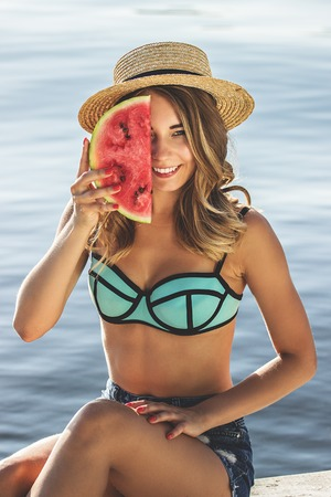 Sweet summertime tastes. Cheerful and young woman in hat and swimsuit keeping watermelon slice against half part of her face while sitting on the beach. Zdjęcie Seryjne