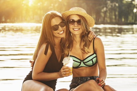Happy best friends spending time together. Two cute, young and attractive women in swimsuits smiling and hugging while sitting on the beach. Zdjęcie Seryjne