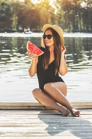 She loves spending summer time on the beach. Young and beautiful woman in swimsuit and hat keeping slice of watermelon in hand while sitting on wooden pier.