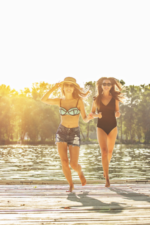 Spending carefree summer time on the beach. Two beautiful and young women in swimsuits running along the wooden pier while having fun outdoors. Zdjęcie Seryjne