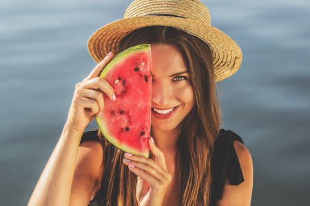 Summertime tastes. Cheerful and young woman in hat and swimsuit keeping watermelon slice against half part of her face while standing outdoors. Zdjęcie Seryjne