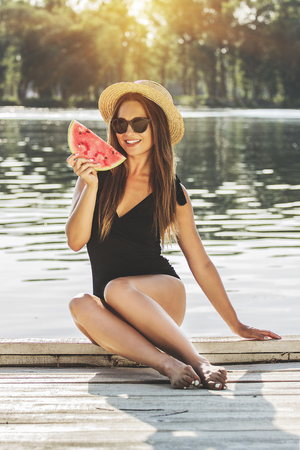 She loves summer time. Attractive young woman in swimsuit and sunglasses keeping watermelon slice in hand and smiling while sitting on wooden pier.