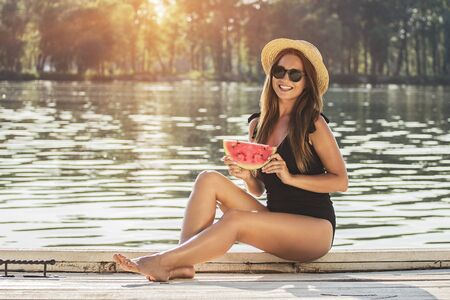 Spending happy summer time outdoors. Beautiful and young woman in swimsuit and sunglasses keeping slice of watermelon in hands and smiling while sitting on wooden pier.