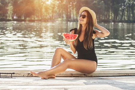 She loves spending summer time on the beach. Young attractive woman in swimsuit and hat keeping slice of watermelon in hands and smiling while sitting on wooden pier.