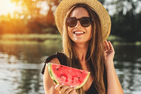 Sweet summer moments outdoors. Closeup of attractive and young woman in hat and sunglasses keeping slice of watermelon in hand and smiling while having fun outdoors.