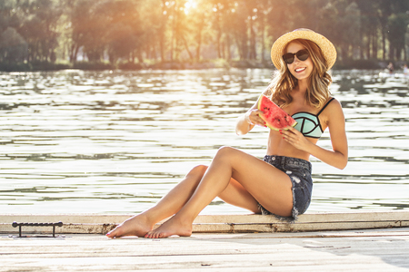 Eating slice of tasty watermelon on the beach. Beautiful blond haired woman in swimsuit and hat keeping slice of watermelon and smiling while sitting on wooden pier. Zdjęcie Seryjne