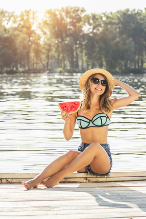 Sweet summer moments outdoors. Attractive young blond haired woman in swimsuit and hat keeping slice of watermelon in hand and smiling while sitting on wooden pier.