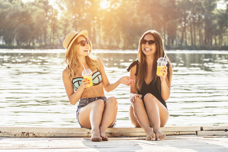 Happy time for gossips on the beach. Two cheerful, attractive and young women in swimsuits drinking orange juice and talking a lot while sitting on wooden pier. Zdjęcie Seryjne