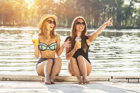 Hey, look over there! Two cheerful, beautiful and young women in swimsuits drinking orange juice and sitting on wooden pier while one of them pointing away.