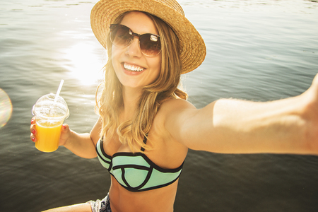 Capturing every happy summer moments. High-angle view of beautiful and young blonde haired woman keeping camera in hand and smiling while taking selfie with orange juice on the beach.