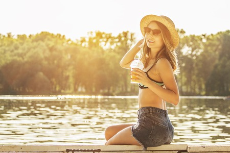 Spending happy summer time outdoors. Side view of young and attractive blonde haired woman in swimsuit and sunglasses keeping orange juice in hand and smiling while sitting on wooden pier. Zdjęcie Seryjne