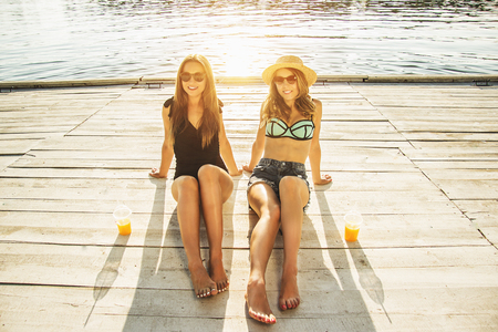Best friends relaxing on the beach. Two beautiful and young women in swimsuits looking to camera and smiling while sitting on wooden pier. Evening sunlight on background. Zdjęcie Seryjne