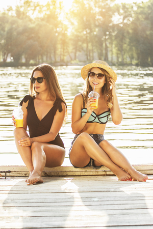Spending good time outdoors. Two beautiful and young women in swimsuits drinking orange juice and having fun while sitting on wooden pier. Zdjęcie Seryjne