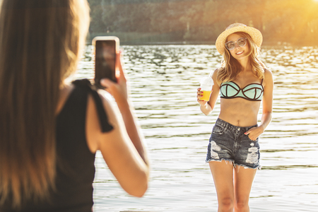 Capturing happy summer moments. Rear view of beautiful and young woman taking photo of her best friend on her smart phone while having fun on the beach.