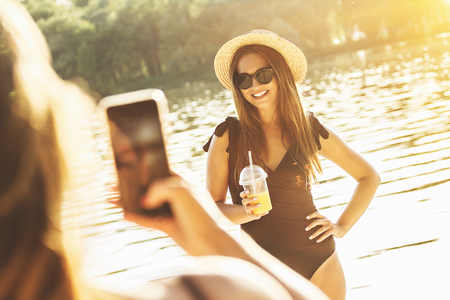 Capturing happy summer moments. Rear view of young and attractive woman taking photo of her best friend on her smart phone while having fun on the beach.