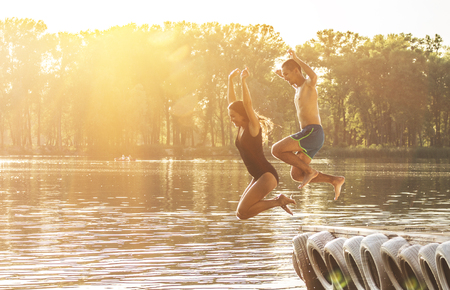 Having summer fun on the beach. Side view of beautiful and young woman jumping into the water from wooden pier with her young friend. Zdjęcie Seryjne