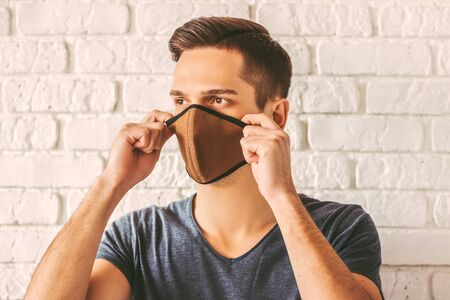 Confident young student wearing face mask for professional personal protection against air pollution or coronavirus nCov-19. Hipster man in protective face mask or respirator for prevention COVID-19