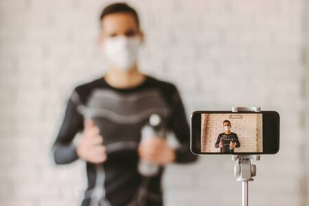 Filming online classes with confident professional fitness trainer. Exercising at home during coronavirus quarantine. Young sports man blogger in medical face mask recording video on phone camera