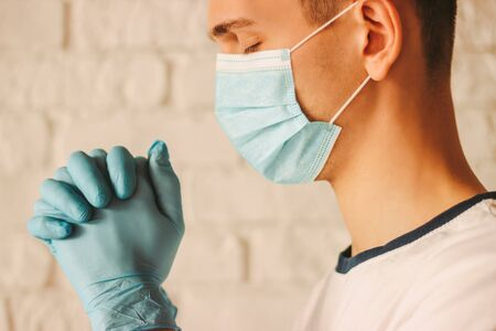 Young religious man in protective face mask and medical gloves praying for help to God in church. Doctor surgeon prayer in medical mask on face and protective gloves in hospital. Coronavirus COVID-19