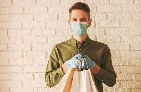 Young delivery man in medical mask on face and protective gloves holding paper bags in hands. Hipster man courier with shopping bags. Safe online delivery service. Coronavirus COVID-19 protection