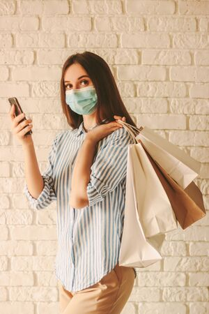 Beautiful happy girl shopper in protective face mask hold mobile phone, shopping bags in hands. Young woman shopaholic in medical face mask shopping online at home. Coronavirus COVID-19 sale, discount