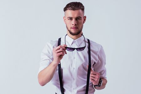 Portrait of charismatic man in white shirt and suspenders holding sunglasses in hand and looking to camera while standing against gray background. Elegant and stylish man in classical clothing