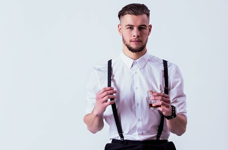 Confident, stylish man in white shirt and suspenders looking to camera and holding glass of whiskey in hand while sitting against gray background. Elegant man drinking alcohol in studio. Men's fashion