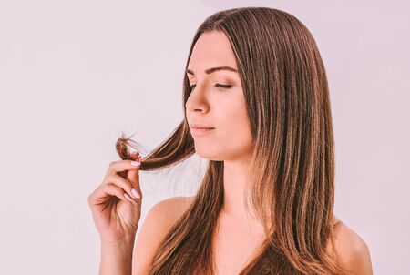 Portrait of young frustrated woman looking at dry split hair tips in her hand isolated. Beautiful sad worried woman with long unhealthy damaged hair in hand. Hair loss problem, hair care, treatment