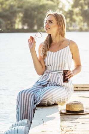 Stylish and beautiful blonde girl in stripped overalls posing at riverside with bottle of lemonade in hand.