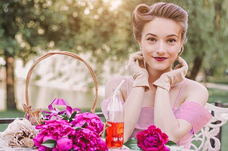 Portrait of happy young attractive woman in stylish pink vintage dress and pin up hairstyle sitting at table on garden and smiling. Beautiful tender romantic retro girl on picnic on summer garden