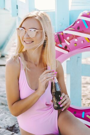 Young beautiful girl have fun and posing on sunny seaside. Cheerful attractive woman in stylish sunglasses and pink swimsuit drink cold lemonade and smile while sit on summer beach. Travel, vacation Standard-Bild