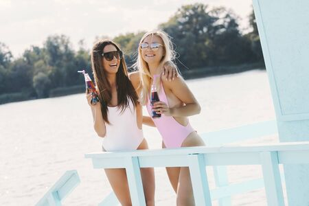 Two young beautiful women friends having fun, laughing and hugging each other while posing at lifeguard tower. Attractive girls in stylish swimsuits and sunglasses drink lemonade on sunny summer beach Standard-Bild