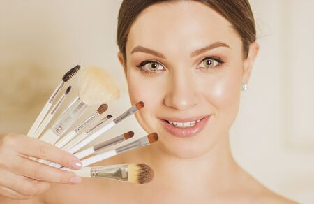 Closeup of pretty young woman holding set of make up brushes near face and smiling. Beautiful cute girl posing with brushes for makeup in her hand. Beauty, cosmetics, grooming, style and fashion