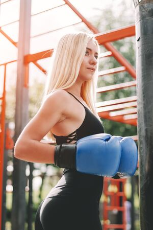 Portrait of blonde fitness girl in boxing gloves posing on sports ground. Beautiful young boxing woman having rest after hard workout outdoors. Sporty girl with doing boxing exercises