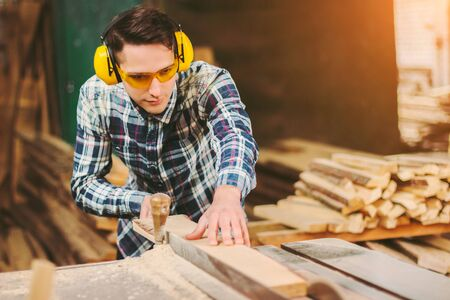 Professional carpenter in protective glasses and headphones using electric circular saw at woodworking workshop. Skilled cabinet maker working with sawing machine at sawmill. Wood production craftsman