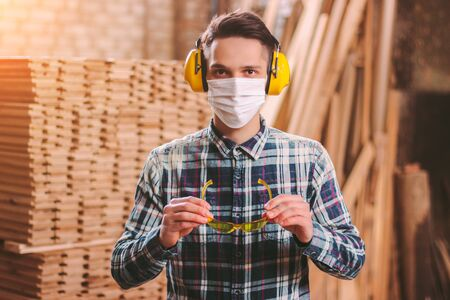 Portrait of professional carpenter wearing medical face mask, hearing protection headphones, protective glasses at sawmill. Male craftsman in protective equipment at wood workshop. Carpentry industry Stock Photo
