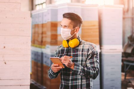 Portrait of man supervisor in medical face mask and protective headphones checking wood material inventory at storage. Young warehouse worker inspecting, counting woodwork stock. COVID-19 quarantine Standard-Bild