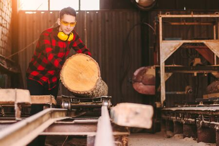 Professional carpenter master in protective glasses and headphones working with cut tree logs to sawmill warehouse. Skilled workman moving wood trunk to sawing machine at lumber production factory
