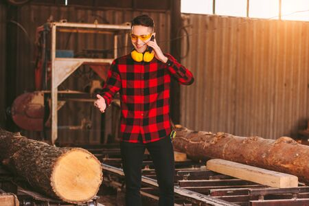 Happy business man in protective glasses and headphones talking mobile phone while working at timber production factory. Professional sawmill workman at woodworking warehouse. Small business owner