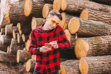 Young workman in protective glasses talking mobile phone and writing to notebook at sawmill factory. Happy wood production mill workman inspect cut tree logs. Wooden material warehouse. Timber storage