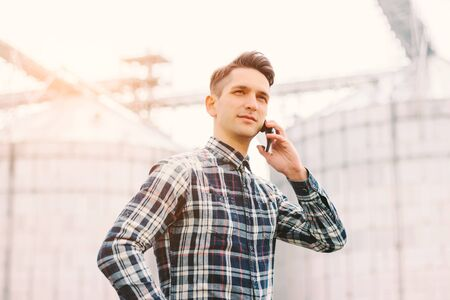Portrait of young business man talking mobile phone while working at silage storage factory. Happy agriculture business manager holding cell phone in hand while standing against silos building