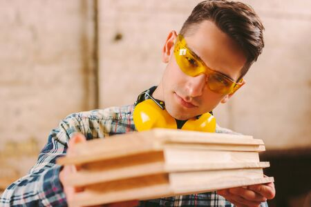 Young male carpenter in protective glasses and headphones checking wooden planks while working at sawmill. Confident craftsman holding stack of wood material. Professional cabinet maker at workshop
