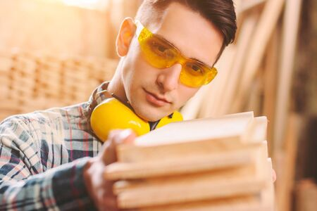 Closeup of confident cabinet maker in protective eyewear and headphones holding stack of wooden material in hands. Young male carpenter working at sawmill. Joiner master at woodworking workshop, DIY