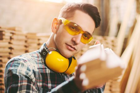 Skilled male cabinet maker in protective glasses, headphones holding stack of wooden planks in hands at sawmill factory warehouse. Professional carpenter at woodworking workshop. Furniture production