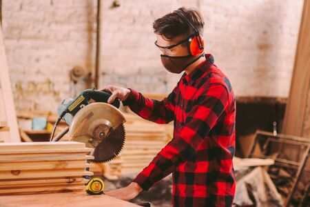 Carpenter in protective glasses, headphones and mask using electric circular saw at sawmill. Professional skilled cabinet maker cutting wood board with circle saw. Woodworking, furniture production
