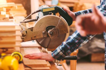 Closeup of professional cabinet makers working with electric circular saw at woodworking workshop. Skilled carpenter cutting wooden board with circular saw. Wood material production. Lumber factory