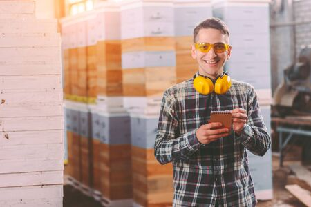 Happy sawmill business owner in protective glasses and headphones writing in notebook while supervising storage inventory. Young warehouse worker inspecting wood material. Woodworking production store